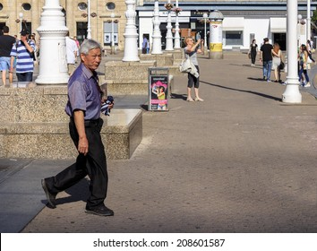 ZAGREB, CROATIA - JUNE 07, 2014: Chinese tourist walking on Zagreb main square Trg bana Jelacic on June 07, 2014