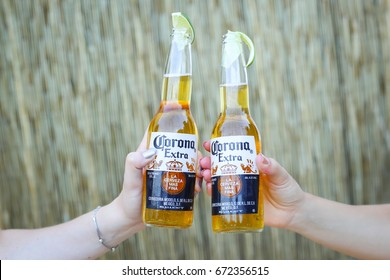 ZAGREB, CROATIA - JUNE 28, 2017 : Two hands with Corona Extra beer bottles on the Corona Sunsets Session party on the roof of Zagreb Dance Center in center of Zagreb, Croatia.