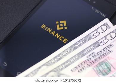 ZAGREB, CROATIA - MARCH 10, 2018. Binance android app on black background with few dollar bills. Binance is a finance exchange market.