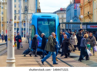 ZAGREB, CROATIA, March 10 2018: People passing by in front of blue tram in downtown Zagreb, Croatia.
