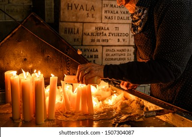 ZAGREB, CROATIA -  MARCH 25, 2019: Lighting candles in Kamenita vrata (Stone Gate) to remember and honor the deceased loved ones.