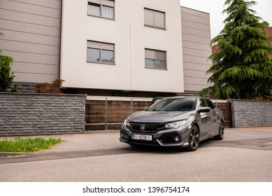 ZAGREB, CROATIA - MAY 12, 2019: New Honda Civic in grey colour in front of the house. New Honda model. Front view of the car.
