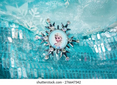 ZAGREB , CROATIA - May 9th , 2015 : Elsa , cartoon character from Walt Disney movie Frozen on the girl dress medallion    ,product shot