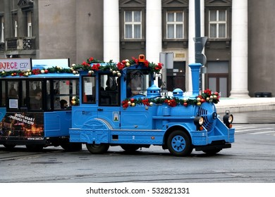 Zagreb, Croatia - November 27, 2016: Small blue train with Christmas decorations driving through streets in Downtown Zagreb. Children train rides are one of many events during Advent in Zagreb Fair.
