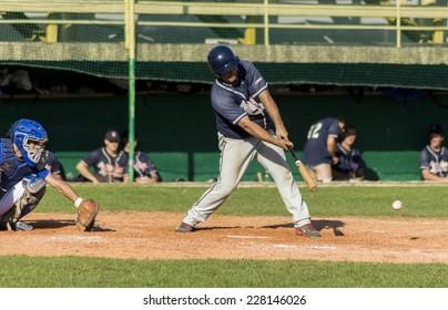 ZAGREB. CROATIA - OCTOBER 12, 2014: Match between Baseball Club Zagreb in blue jersey and Olimpija in dark blue jersey. Unidentified batter hits ground ball