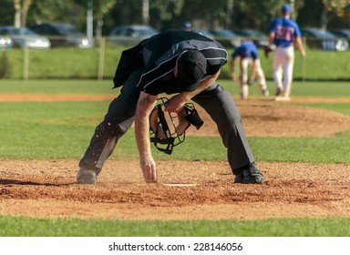 ZAGREB. CROATIA - OCTOBER 12, 2014: Match between Baseball Club Zagreb in blue jersey and Olimpija in dark blue jersey. Plate umpire cleaning the base