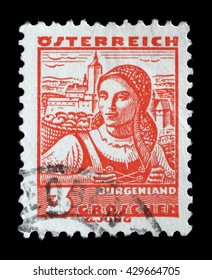 """ZAGREB, CROATIA - SEPTEMBER 13: A stamp printed in Austria shows a woman in the Austrian national dress with the inscription """"Burgenland"""" circa 1934, on September 13, 2014, Zagreb, Croatia"""
