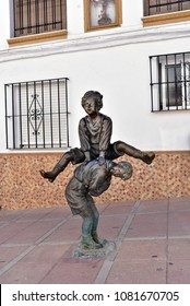 ZAHARA  SPAIN / 04.01.2017: Statue of the two children playing leapfrog, Zahara village in Cadiz, Spain