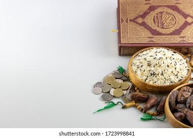 Zakat-Konzept. Mischung von weißem, braunem und schwarzem Reis in Schüssel.Date Palm in Schüssel.Münzen, Rosenkranz, Heiliger Koran auf weißem Hintergrund.