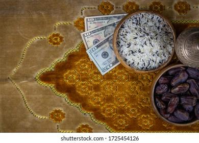 Zakat-Konzept. Mischung von weißem, braunem und schwarzem Reis in Schüssel.Datum Handfläche in Schüssel. Geldbeutel, Rosenkranz, Heiliger Koran auf persischem Teppichboden. Konzept: Religion, Urlaub
