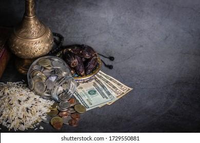 Zakat-Konzept. Mischung von weißem, braunem und schwarzem Reis in Schüssel.Datum Handfläche in Schüssel. Geldbeutel, Münze in einer Glasflasche, Rosenkranz, Heiliger Koran auf Marmorschwarzem Hintergrund. Konzept: Religion, Urlaub