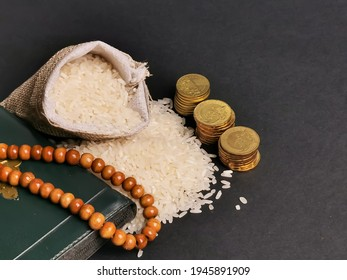 Zakat concept. Selective focus rice in sack with coins,rosary and Koran. Zakat is a mandatory process for Muslims and is regarded as a form of worship.