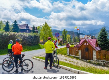 ZAKOPANE 05-22: Pedestrians taking rest and looking at amazing landscape of regional houses and remote mountains under cloudy sky in Zakopane, Poland on May 05, 2020