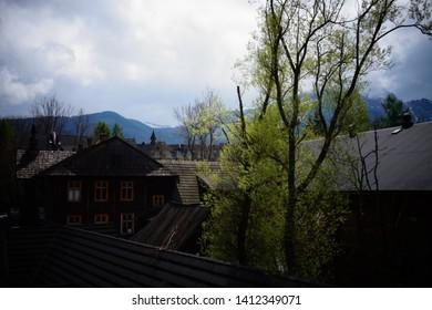 Zakopane, Malopolskie, Poland - 18 May 2019: Typical wooden house architecture of Zakopane, with Tatra Mountains in the background
