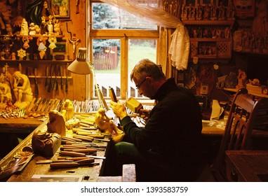 Zakopane, Podhale region / Poland - August 2016. A man carves figures in his workshop in Zakopane, Poland.