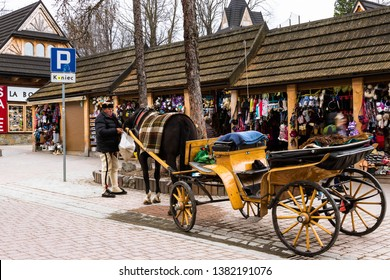 Zakopane Poland, 4/11/19: Main street of the city called Krupowki. The coachman feeds his wagon horse in front of the wooden boutiques. selling souvenirs.