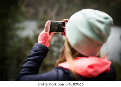 ZAKOPANE, POLAND DECEMBER 02, 2017: Girl taking photo of a mountain using iPhone 7 Rose Gold color