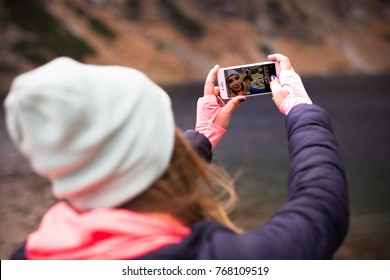 ZAKOPANE, POLAND DECEMBER 02, 2017: Girl taking selfie photo in a mountains using iPhone 7 Rose Gold color
