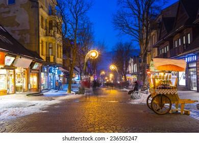 ZAKOPANE, POLAND - DECEMBER 4, 2014: Famous Krupowki street in Zakopane at winter time. Krupowki street is the main shopping area and pedestrian promenade in the center of Zakopane, Poland.