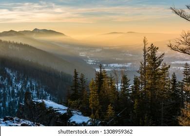Zakopane, Poland - February 06, 2019: Evening smog lit by the setting sun over the valley and towns of Podhale (among others Zakopane, Koscielisko). Tatra Mountains.