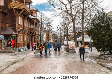 Zakopane, Poland - February 22, 2019. A crowd of people is walking along Krupowki street on an winter day. Krupowki street is the main city promenade in Zakopane. The street is filled with souvenir sh