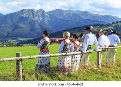 ZAKOPANE, POLAND - JULY 29, 2016: Loacal people in traditional clothes in Zakopane. Colorful and decorated with bright red colors clothes are traditional for Zakopane area in Poland.