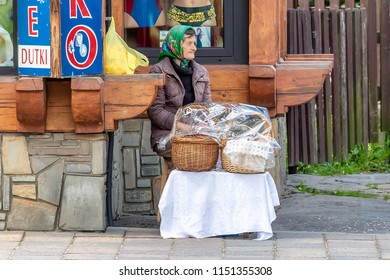 """Zakopane, Poland June 4, 2018: Old woman covering her head sits by the side of road for selling food in the town of Zakopane that is known informally as """"the winter capital of Poland"""""""