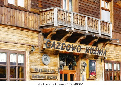 ZAKOPANE, POLAND - MARCH 06, 2016: Restaurant's name over the entrance to Gazdowo Kuznia located in wooden building which until 1898 was the biggest hotel in Zakopane, nowadays it houses a restaurant