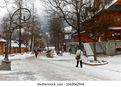 Zakopane, Poland - March 19, 2018: Only a few pedestrians walk along the famous promenade. On both sides of Krupowki Street there are buildings and on the surface of the pavement lies snow