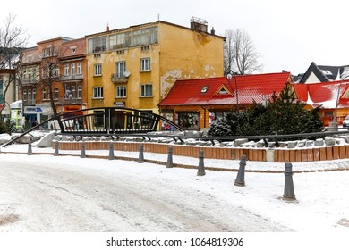 Zakopane, Poland - March 19, 2018: The city's landscape during the winter day. Old tenement houses and other architectural objects can be seen