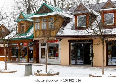 Zakopane, Poland - March 19, 2018: The wooden building at Krupowki Street dates back to about 1905, and on the ground floor there are shop windows. There are no leaves on the trees, it is winter.