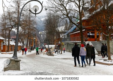 Zakopane, Poland - March 19, 2018: Krupowki Street with its unique streetlights is the main promenade of the city. Along this street there are many wooden and brick buildings.