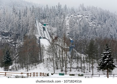 Zakopane, Poland - March 20, 2018: Three Ski Jumps are seen on a natural hillside among forest areas. During the winter season everything is covered by snow.