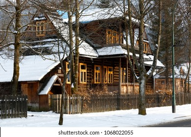 Zakopane, Poland - March 21, 2018: Behind the trees and the wooden fence there is a wooden villa locally called Koszysta. This historic building dates back to 1902.