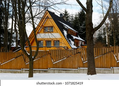 Zakopane, Poland - March 21, 2018: The wooden building hidden behind the wooden fence is covered with a steep roof. Around there are some trees without leaves because it is wintertime.