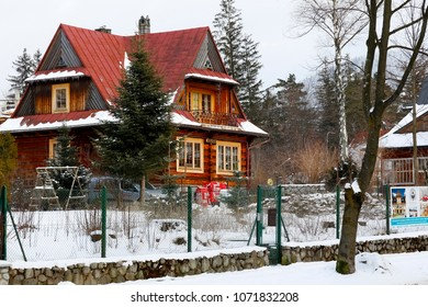 Zakopane, Poland - March 21, 2018: A wooden villa with a steep red roof is seen on a winter day on a fenced property.