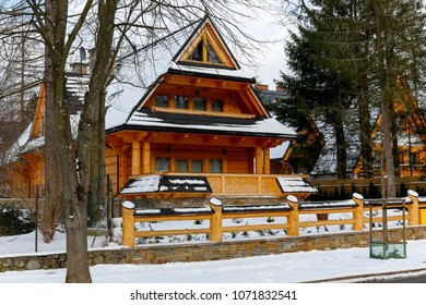 Zakopane, Poland - March 21, 2018: During winter season, a log house with a steep roof can be seen in the area fenced with a wooden fence.