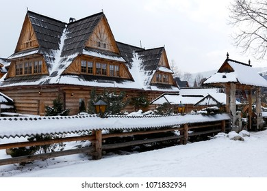 Zakopane, Poland - March 21, 2018: A large wooden log building with a traditional sloping roof covered with wooden shingles. It is visible here during a cloudy winter day.