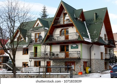 Zakopane, Poland - March 21, 2018: A brick building with sloping roofs, which is green in colour, is a guest house under the local name of Willa Karpinskich