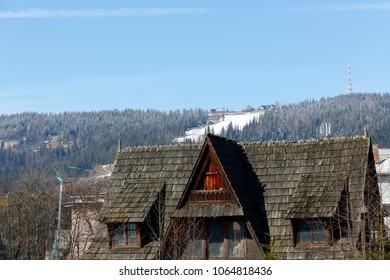 Zakopane, Poland - March 22, 2018: Above the roof of the house is visible a hill called Gubalowka. The roof of this abandoned house is covered with shingles that seem to be decaying.