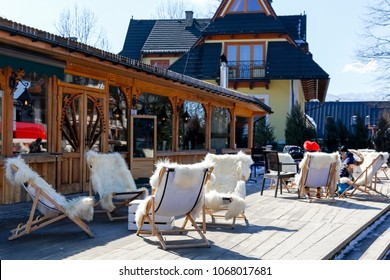 Zakopane, Poland - March 22, 2018: On the platform located in front of the entrance to the regional restaurant there are several deck chairs. There are people who can be seen in a distance