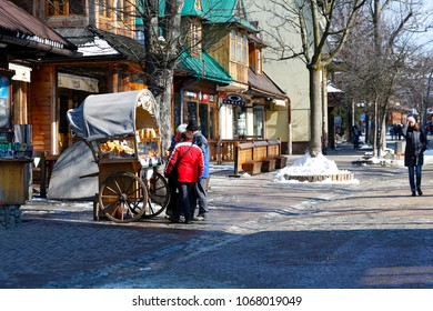 Zakopane, Poland - March 22, 2018: On the pavement, by the buildings, there is a small movable stand for the sale of local cheeses and other products. There are people who are watching something there