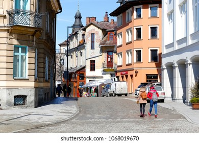 Zakopane, Poland - March 22, 2018: People are walking on the cobbled street. There are several buildings around and several cars parked there.