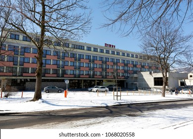 Zakopane, Poland - March 22, 2018: A large building houses a recreation center, in front of which there is a large parking lot but only a few cars parked there. This building is known locally as Hyrny