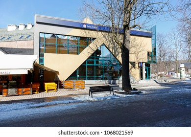 Zakopane, Poland - March 22, 2018: Contemporary building that was built in 1993 houses a branch of the bank. The plastered facade of the building is varied by large windows of unusual shape.