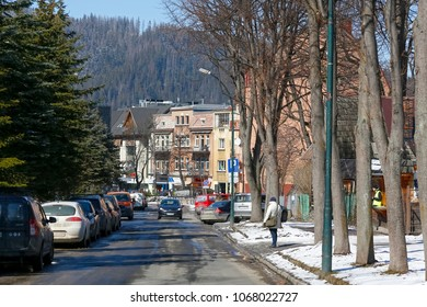 Zakopane, Poland - March 22, 2018: At the end of the street there are tenements. Trees and several cars parked can be seen, people are there as well