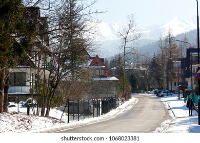 Zakopane, Poland - March 22, 2018: There is a narrow street between the houses in a quiet district. In the distance you can see snow-covered hills.