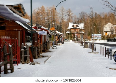 Zakopane, Poland - March 22, 2018: Along the sidewalk there are commercial pavilions which, due to the low season, are now largely closed. There are houses visible from afar.