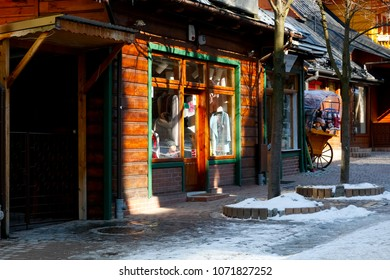 Zakopane, Poland - March 22, 2018: Shop window with clothes on sale visible inside. It is in a wooden building, which is located by the Krupowki street, which is the main shopping street in the city.
