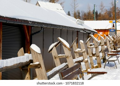 Zakopane, Poland - March 22, 2018: Along the pavement, behind a stylish wooden fence, there are commercial pavilions, which due to the low season are now closed. There is a lot of snow.